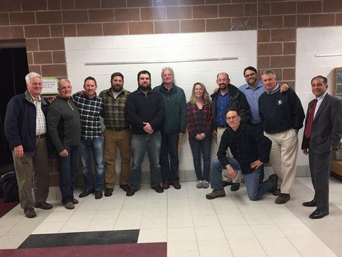 Group of men standing in arc-shaped row  - members of School Modernization Building Committee Team