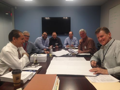 Group of Men sitting atrectangular table in meeting at State with Office of Construction Grants